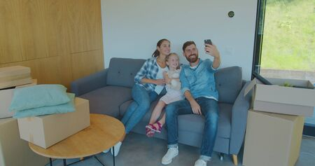 Beautiful family making memorable selfies on smartphone while relaxing, sitting between cardboard boxes after house move.