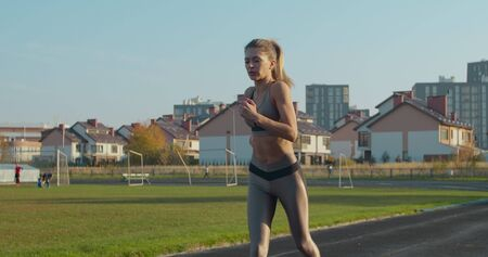 Woman running at a stadium in sunny day.