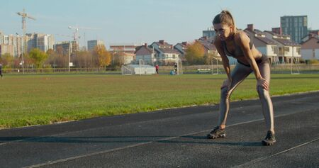 Athletic blonde woman finishing running and bending over to catch her breath.