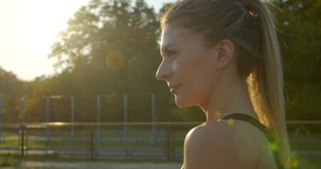 Portrait of Woman running at a stadium in sunny day.