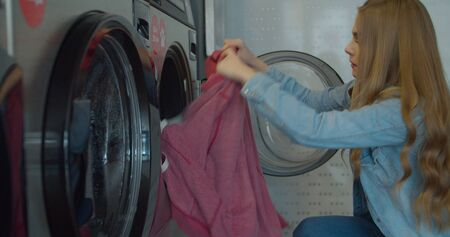 Woman take away laundry clothes. Self-service public laundry