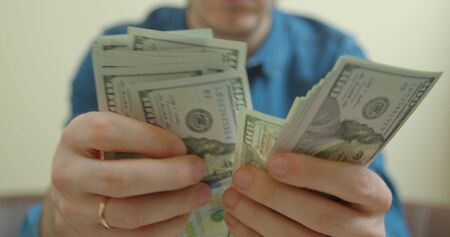 Person counts 100 dollar banknotes in hands. White background. Stitch of money. Rich man. Thousands of dollars.