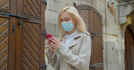 Young woman in protective mask using smartphone in the street of old city. Worried girl searching news about Covid-19. Pandemic Covid-19 coronavirus protection.