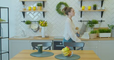 Energetic dancing of a happy girl. Pretty young woman dancing in kitchen and listening music. Beautiful woman listening to music on smartphone.