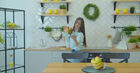 Young attractive woman in positive mood is dancing in kitchen, wearing wireless headset, listening music, having fun at home.