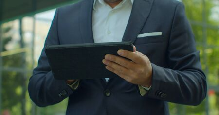 Close up of Man Holding Modern digital tablet. Businessman Typing on his digital tablet. businessman read news on Tablet Computer. Classical Black Suit.Business Lifestyle 版權商用圖片