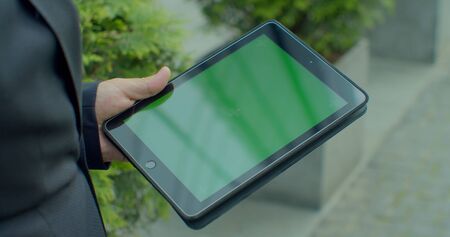 Overhead view businessman browsing internet online on digital tablet outdoors. Close up business man working on touchpad on street. Male hands typing on pad with green screen in slow motion
