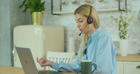 Beautiful Young Caucasian Woman Wear Headphone Communicating Video Conference Call Speak Looking at Computer Home Office Concept Interview Call Center Helpdesk Slow Motion Quarantine Job.