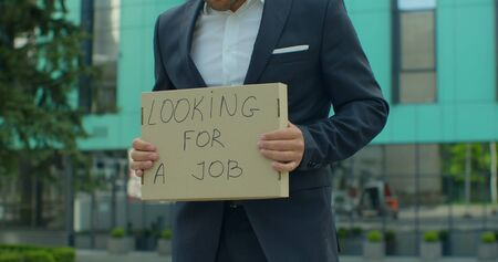 """Close up Portrait shot of a young businessman in a suit standing near office center with a sign """"looking for job""""."""