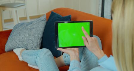 Woman Using Gestures with Touchscreen Device, Browsing Internet, Watching Content. Woman at Home Resting on a Couch Using with Green Mock-up Screen Tablet Computer in Horizontal Landscape Mode