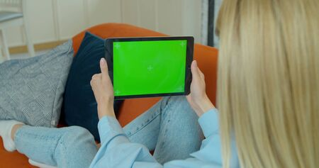 Pretty girl making video call on Digital Tablet. Woman at Home Uses Green Mock-up Screen Digital Tablet. She's Sitting On a Couch in His Cozy Living Room