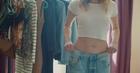 Woman in jeans showing off weight loss
