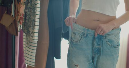 Woman in jeans showing off weight loss. 免版税图像
