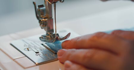Phased sewing of medical masks from blue fabric on a sewing machine. Close up industrial sewing machine makes a seam. The concept of deficiency of medical masks during the coronavirus pandemic. Banco de Imagens