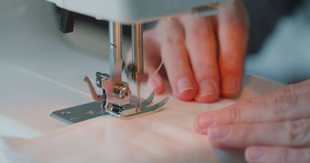 Close up of woman fingers sew on sewing machine. Details of sewing machine. Woman is overlocking textile. Workshop in sewing fabric. Creation and tailoring clothes.