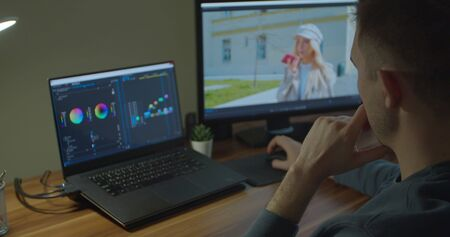 Man working on computer with Two Monitors Color Correction Post Production video or photo in Progress Closeup Banque d'images