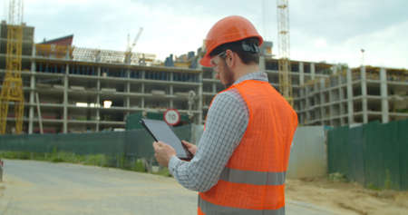 Close-up portrait of engineer with gadget on background of building under construction. Modern construction engineer or architect in helmet at construction site works with industrial electronic tablet