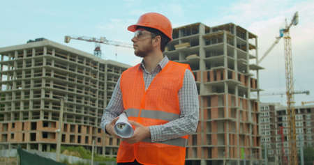 Portrait of an architect or builder in hard hat standing in front of building under construction. Close-up portrait of engineer with blueprint on background of building under construction.