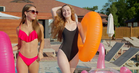 Hot pretty girls in bikini with inflatable, walking by the pool. Attractive fitted women in swimsuits have fun on summer party at resort.