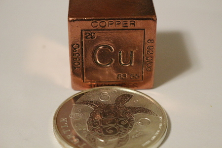 A copper cube next to a silver coin