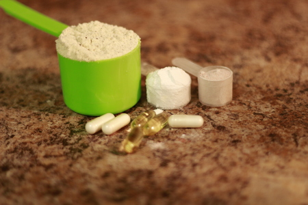 Whey protein powder in scoop with vitamins and on granite background. Selective focus,