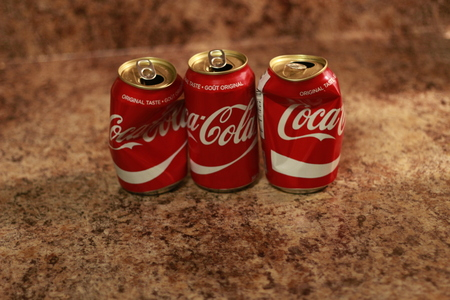 Editorial Illustrative photo of Crumpled Coca Cola can. Coca Cola drinks are produced and manufactured by The Coca-Cola Company, an American multinational beverage corporation.