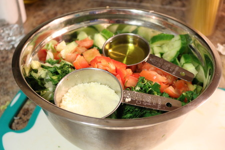 oil and salad showing measuring cups with olive oil and parmesan cheese as a dressing for this salad very colourful and nice example of a healthy salad Stock Photo