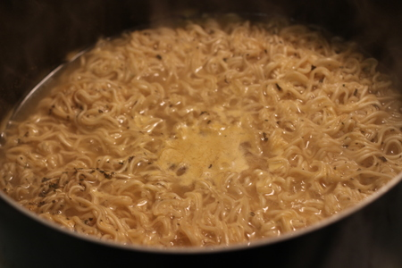 Ramen is a Japanese dish. It consists of Chinese-style wheat noodles served in a meat or fish-based broth, often flavored with soy sauce or miso, and uses toppings such as sliced pork, dried seaweed, menma, and green onions Banco de Imagens