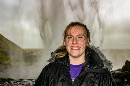 Young tourist, 20 to 25 years old poses behind a waterfall in Iceland. Embrace nature, and carefree Reklamní fotografie