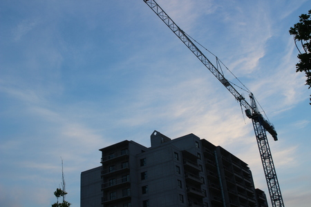 Building crane and building under construction. Construction site. Construction cranes and high rise building under construction against cloudy sky Stock Photo