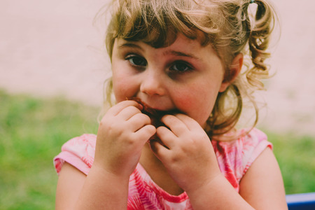 little girl in pink sweater outdoors acting shy