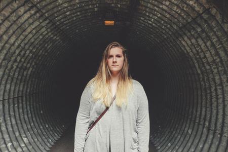 woman tunnel walk alone dark underspass, abstract concept of dar Stock Photo