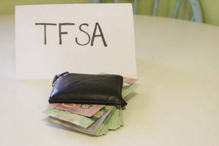 a sign that says TFSA next to a wallet that has money in it. Theme of Canadian savings. TFSA stands for tax free savings account