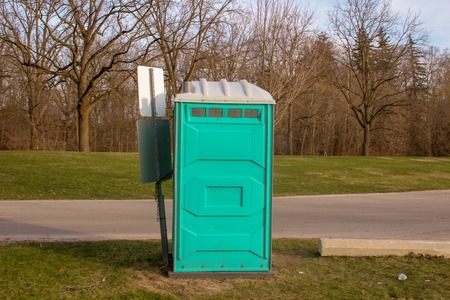 A Dirty, Blue Portable Toilet in a Park, nasty looking place to