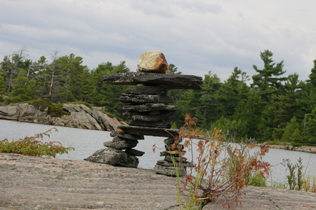 inukshuk rocks lake. forest and lake in background 스톡 콘텐츠