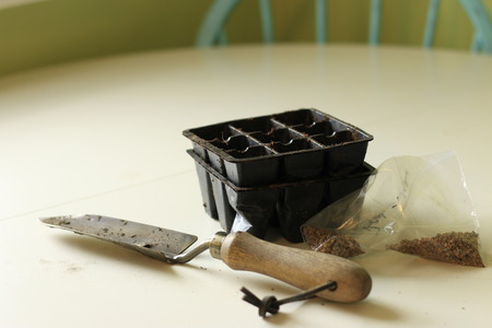 A bag of seeds next to a small shovel and modules for seed starting. Gardening concept and spring sowing concept..