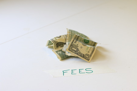 US 1 dollar bills next to a note that says fees. Concept of bank fees or other unfair fees that cost money