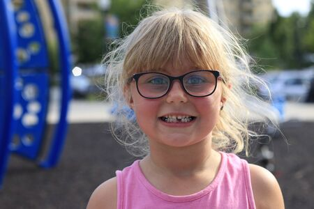 Little girl smiling outside showing her missing middle tooth