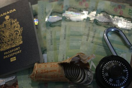 A lock and passport with Canadian money. Theme of politics and opening citizenship.