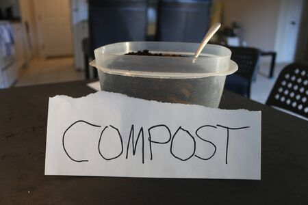 Photo of a container of used coffee grounds with a sign that says compost.