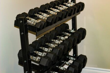 Every size of dumbbell on its rack in a fitness room. Is provided for customers, villagers or livers practice weight training exercise for their muscle strength.