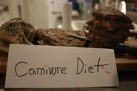 Carnivore diet concept. Raw ingredients for zero carb diet - meat, poultry, fish, seafood, eggs, beef bones for bone broth and copy space in center on gray stone background. Top view or flat lay..