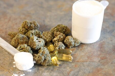Buds of marijuana next to a scoop of protein and creatine with fish oil pills in front.
