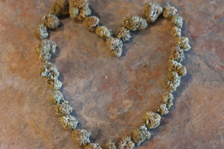 The shape of a heart made out of cannabis buds .