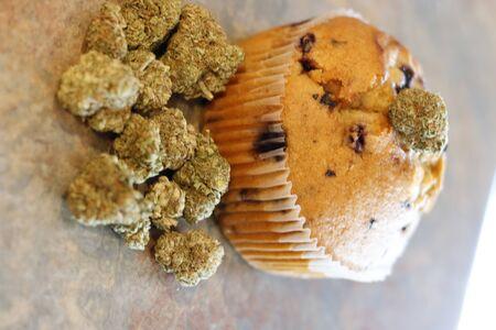 A cannabis muffin next to a bunch of marijuana buds.