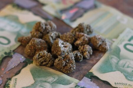 Marijuana and canadian money on a granite counter.