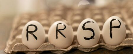 the acronym RRSP wrote on eggs. It stands for Registered Retirement Savings Plan. Фото со стока