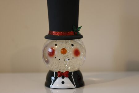 Christmas snow globe with knitting clothes on blurred background. Space for text. Фото со стока
