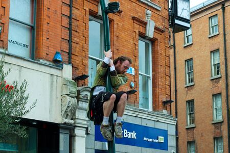 Dublin, Ireland - February 19th 2018: A street performer is on a unicycle doing a performance on Grafton street. The informal economy is a central point of the Dublin tourist industry. This informal sector provides the unemployed, or people who are strugg