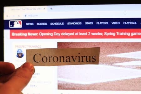 London Canada, March 12 2020: editorial illustrative photo of coronavirus in front of MLB website. The mlb has been postponed